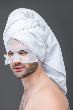 handsome man with towel and collagen mask, isolated on grey, skin care concept Reklamní fotografie