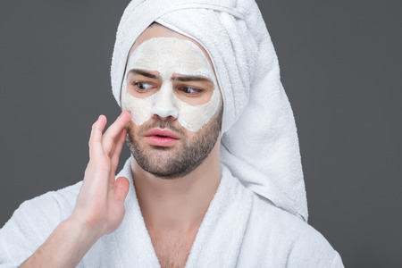man in bath robe and towel with clay mask on face, isolated on grey, skin care concept