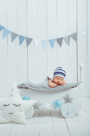 portrait of adorable infant baby in hat sleeping in wooden baby cot decorated with stars Stock Photo