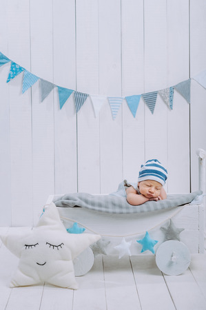cute newborn baby in hat sleeping in wooden baby cot with star pillow near by Archivio Fotografico