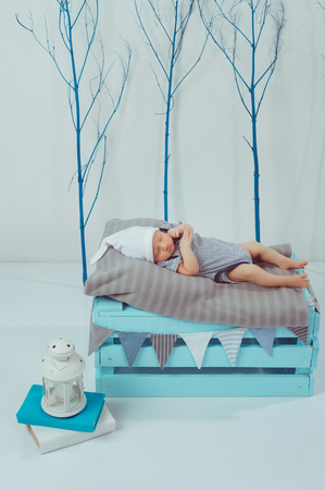 adorable newborn baby in bodysuit and hat sleeping on wooden box with lantern near by Banco de Imagens
