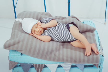 portrait of cute little sleeping baby in bodysuit and hat