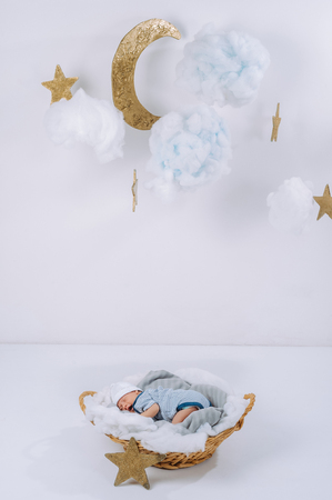 adorable newborn baby sleeping in basket with decorative clouds, moon and stars above head Banco de Imagens