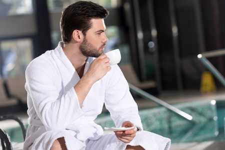 handsome young man in bathrobe drinking coffee and looking away in spa center