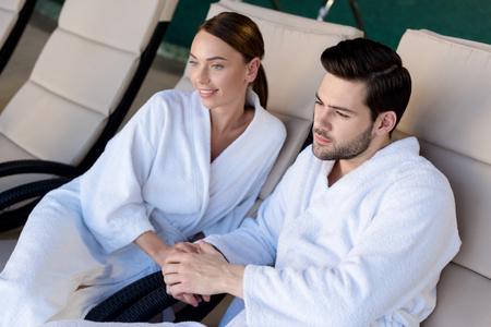 happy young couple in bathrobes holding hands and looking away in spa center Stock Photo