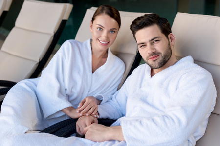 happy young couple in bathrobes smiling and camera in spa center