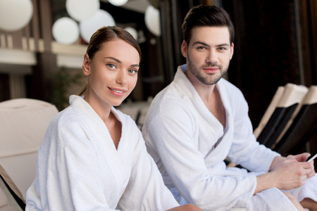 beautiful young couple in bathrobes smiling at camera in spa center