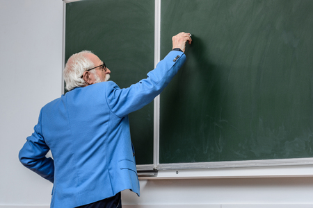 rear view of senior lecturer writing something on blackboard with piece of chalk Фото со стока
