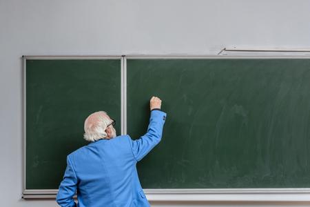 Rückansicht des leitenden Dozenten, der mit Kreide etwas auf die Tafel schreibt