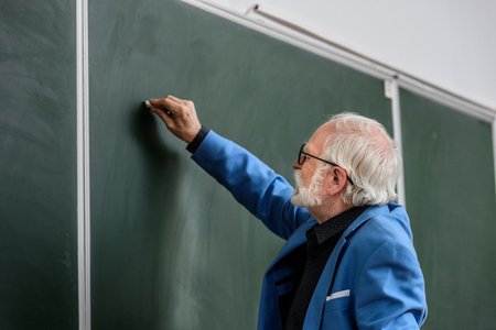 side view of senior lecturer writing something on blackboard with piece of chalk Reklamní fotografie