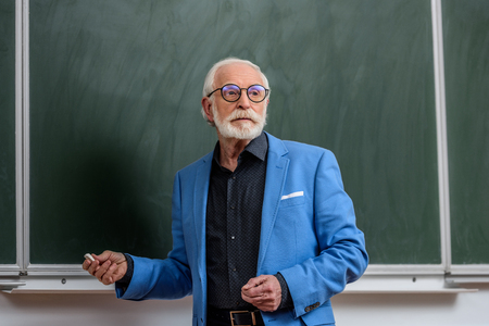 senior lecturer holding piece of chalk and looking away Фото со стока
