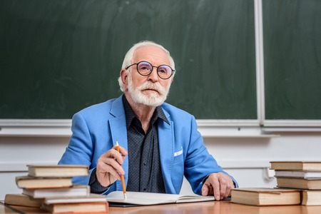 thoughtful senior lecturer sitting at table with pencil and notebook
