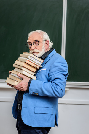 grey hair professor holding stack of books