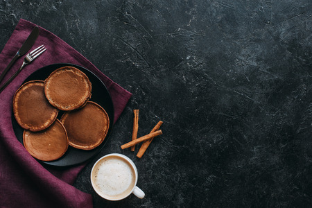 top view of chocolate pancakes and cup of coffee on black concrete table