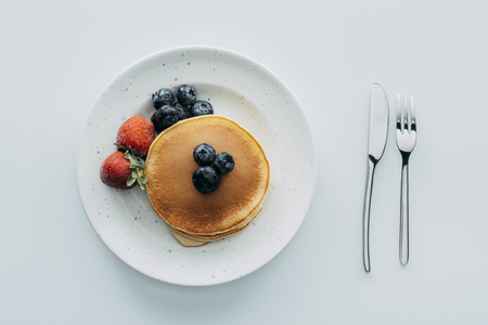 top view of pancakes with blueberries and strawberries on white table Banco de Imagens