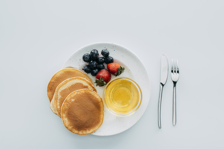 top view of pancakes with berries and maple syrup on white table