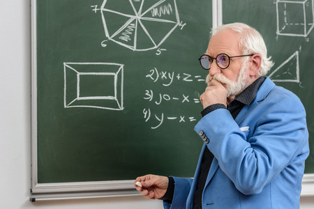pensive grey hair professor standing at blackboard with piece of chalk Banque d'images