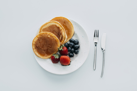 top view of plate of pancakes with berries and cutlery on white table
