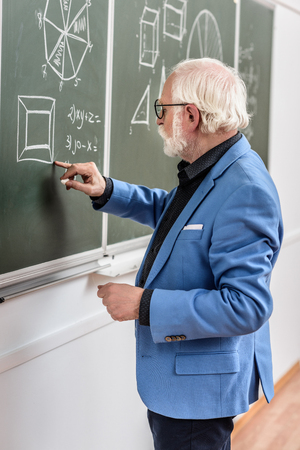grey hair professor correcting something at blackboard