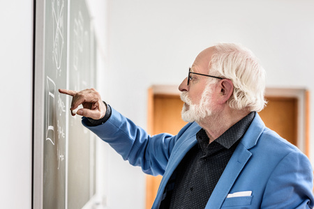 side view of grey hair professor correcting something at blackboard Reklamní fotografie