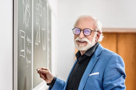 smiling grey hair professor holding piece of chalk