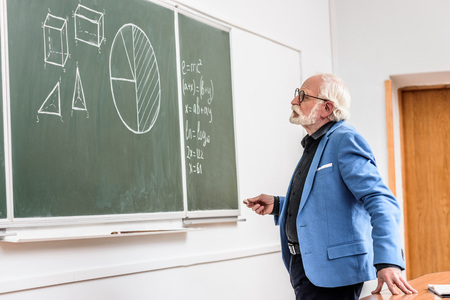 grey hair professor holding piece of chalk and looking at blackboard Фото со стока