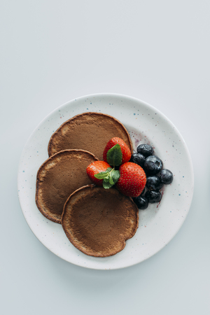 top view of chocolate pancakes with berries on white table