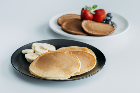 close-up shot of plates of tasty pancakes with fruits on white table
