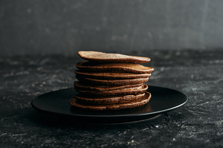 stack of delicious chocolate pancakes on black plate