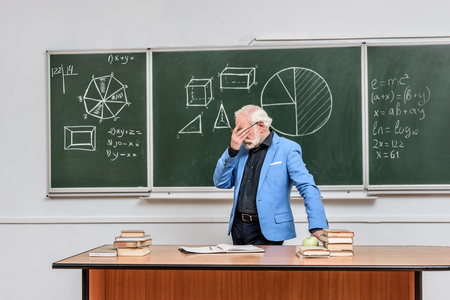 tired grey hair professor touching eyes at blackboard