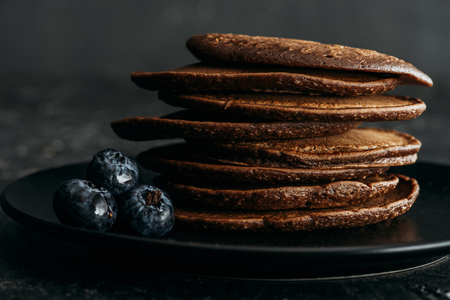 close-up shot of stack of chocolate pancakes with blueberries