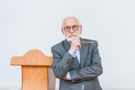zamyślony starszy wykładowca stojący z ołówkiem na białym tle