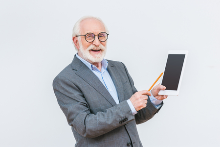 smiling senior lecturer pointing on tablet isolated on white