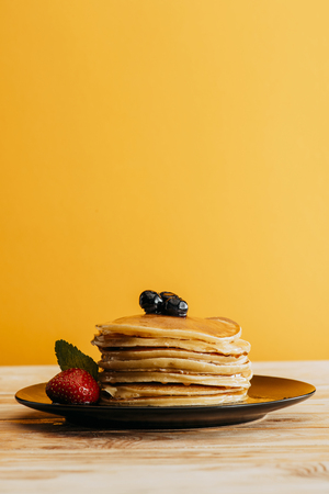 stack of delicious pancakes with berries on yellow