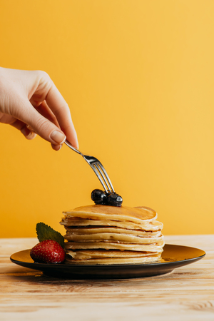 cropped shot of woman taking pancakes from stack with fork