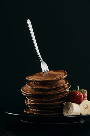 delicious stacked pancakes pierced with fork on black