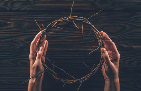 cropped image of woman holding crown of thorns in hands Фото со стока