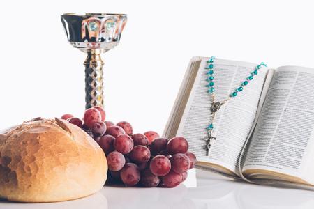 open holy bible, food, chalice and christian cross on white for Holy Communion