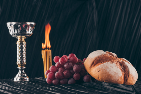 bread with grapes, chalice and candles on black fabric, Holy Communion Stock fotó