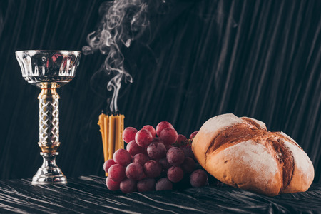 bread, grapes, candles and chalice on dark fabric for Holy Communion