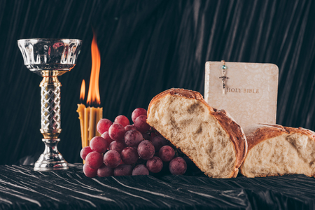 bread, bible, chalice and christian cross on black table, Holy Communion