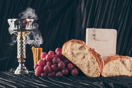 bread, candles, chalice and christian cross on dark table for Holy Communion