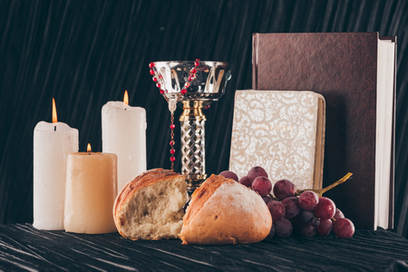 candles, chalice, holy bible, bread and grapes for Holy Communion