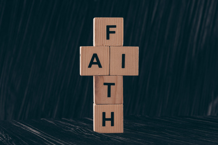 wooden cubes in shape of cross with word Faith on black table