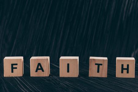 wooden cubes with word Faith on dark table