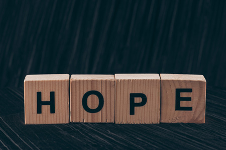 wooden cubes with word Hope on black table