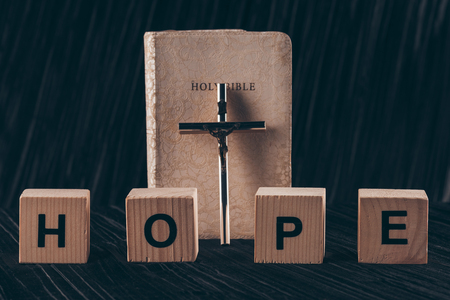 wooden cubes with word Hope and bible with cross on black table Stock Photo