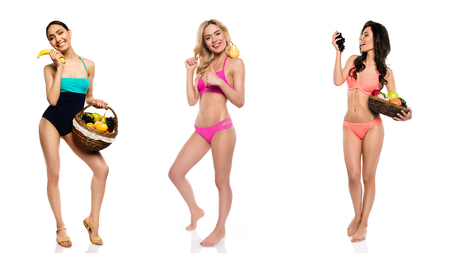 multicultural young women in swimming suits with fruits isolated on white Stock Photo