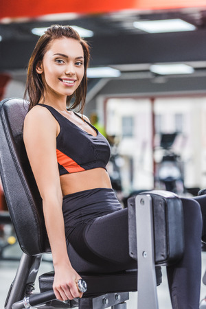 happy young woman exercising on gym machine and looking at camera Stock fotó