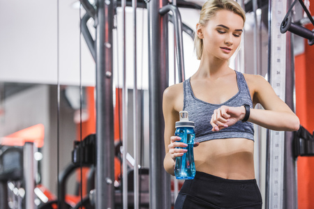young woman checking fitness tracker after workout at gym